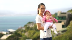 Asian mother with baby on a hill top overlooking the sea Stock Footage