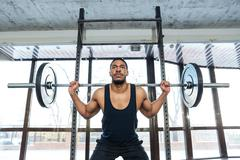 Handsome muscular weightlifter at gym doing squats - stock photo
