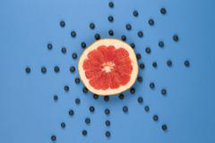 Grapefruit looks like a sun with rays of blueberries Stock Photos