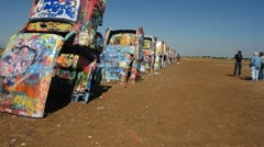 Tourists paint graffiti at the Cadillac Ranch in Texas Stock Footage