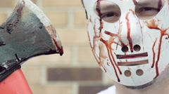 Killer holding bloody ax and wearing mask slow motion Stock Footage