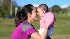 Asian mother doing a nose rub with her baby in park in slow motion Stock Footage