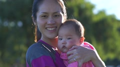 Asian mother w baby in park slow motion in setting sun Stock Footage