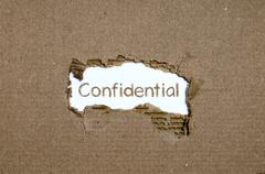 The word Confidential appearing behind torn paper. - stock photo