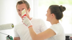 Beautiful couple paint the walls in a new apartment, laughing and having fun Stock Footage
