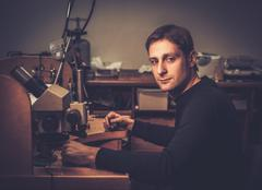 Jeweler sitting at his workplace in a workshop. Stock Photos