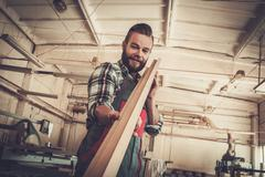 Carpenter doing his job in carpentry workshop. - stock photo