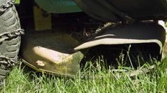 Riding lawnmower blade spitting out grass in slow motion Stock Footage