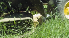 Lawn mower blades cutting grass in slow motion - stock footage