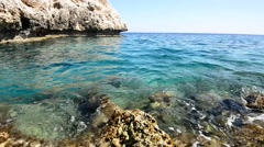 Transparent turquoise sea splashes near the rocky shore Stock Footage