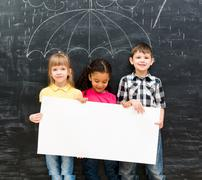 Three cheerful children holding white empty paper sheet Stock Photos