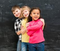 three different children stand one by one peeking out from behind each other - stock photo