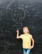 cute little girl pointing on a drawn lamp - stock photo