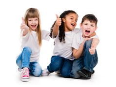 Three funny children sitting on the floor with thumbs up Stock Photos