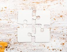 Four connected white puzzle pieces on table Stock Photos