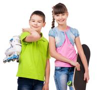 smiling boy and girl with skate and rollers - stock photo