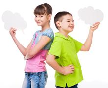 cute boy and girl holding scraps of paper - stock photo