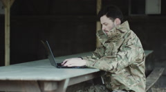 Army soldier on laptop at base camp Stock Footage