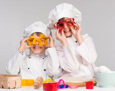 Two funny children play in the kitchen Stock Photos