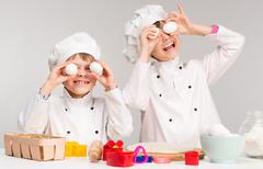 Little boy and girl in cook form holding eggs Stock Photos