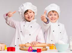 two smiling children in the kitchen with thumbs up - stock photo
