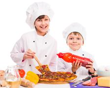 Two little cooks portioning cooked pizza Stock Photos
