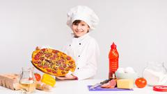 Little smiling girl-cook with big pizza in hands Stock Photos