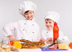 two little cooks portioning cooked pizza - stock photo