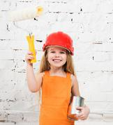 Little girl-worker with paint and roller in hands Stock Photos