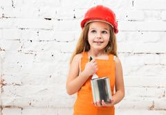 Cute little girl in orange uniform with paint tin in hands Stock Photos
