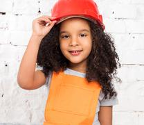 little girl in orange repairmen uniform - stock photo