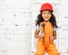 little girl in helmet with hammer and screwdriver - stock photo