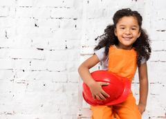 little girl in repairman uniform with helmet in hands - stock photo