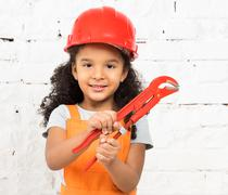 smiling little girl-worker with pliers in hands - stock photo