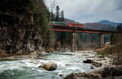 landscape in Carpathian mountains with river and railway bridge - stock photo