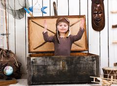 funny little girl-pilot in old chest - stock photo