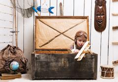 little girl in chest with wooden plane in hands - stock photo