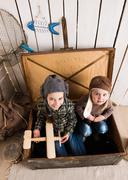 Two funny little girls inside big wooden chest Stock Photos