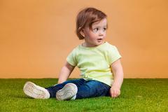 One cute baby girl on orange background - stock photo