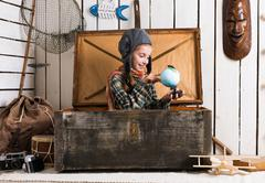 little girl-pilot in wooden chest watching globe - stock photo