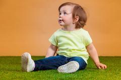 One cute baby girl on orange background Stock Photos