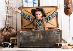 smiling little girl with hands up sitting in big wooden chest - stock photo
