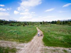 little girl rides bicycle on country road - stock photo