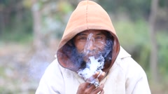 Portrait of an unknown beggar who smokes a cigarette outdoors, Myanmar. Burma Stock Footage