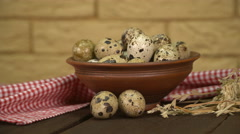 Quail eggs in ceramic bowl on the old wooden table. - stock footage