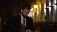 Casual young businessman talking on smart phone at night. Slow motion Stock Footage