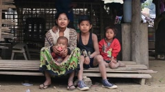 Poor family sits on the street. Poverty is a major issue in Burma - stock footage