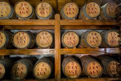 Rum wooden barrels at storage room Stock Photos