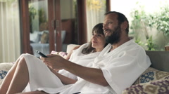 Young couple in bathrobe watching TV while sitting on sofa in outdoor villa Stock Footage