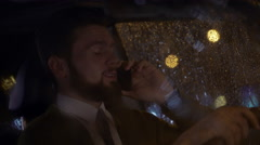 Casual young businessman talking on smart phone at night in his car Stock Footage
